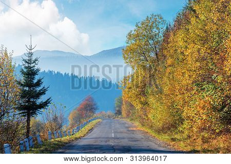 Old Cracked Asphalt Road In Mountains. Straight Path Along The Forest On Hill. Trees In Fall Colors.