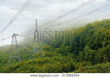 High Voltage Power Lines Tower In Mountains.  Energy Delivery Background. Efficient Electricity Deli