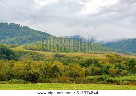 Rural Area In Mountains At Dawn. Agricultural Fields In Early Autumn. Overcast Rainy Weather. Tradit