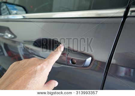 A Woman Using Her Finger To Lock A Car Door Keylessly. Keyless Entry Car Key.  A Keyless Entry Syste