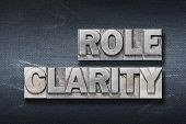 role clarity phrase made from metallic letterpress on dark jeans background poster