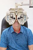 A man checks eyesight in a clinician oculist. Man checks his vision on the machine checking patient vision at eye clinic or optics store. Male patient to check vision in ophthalmological clinic poster