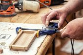 Close-up senior carpenter glueing wooden craft surface and joining with clamps. Woodwork carpenter with equipment and tools at workshop. Handmade diy furniture.Wood part glue joiner poster