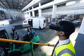 Close-up of Caucasian male supervisor using virtual reality headset in warehouse. This is a freight transportation and distribution warehouse. Industrial and industrial workers concept poster