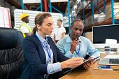 Side view of Caucasian female manager and African-american male supervisor discussing over clipboard at desk in warehouse. This is a freight transportation and distribution warehouse. Industrial and poster