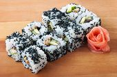 Black California sushi rolls on wooden plate poster