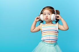Happy Smiling Child Enjoys Listens To Music In Headphones Over Colorful Bleu Background. Vivid And F