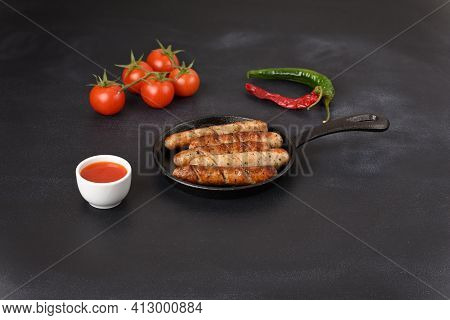 Fried Sausages In A Frying Pan With Hot Chilisous Sauce And Tomatoes.