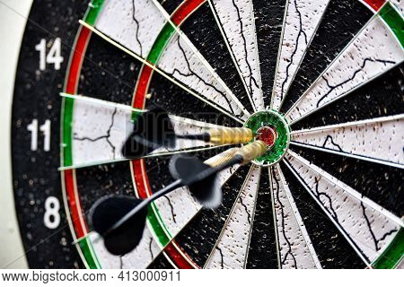 Dart Board With Darts In The Center.