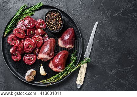Sliced Raw Turkey Hearts Ready For Cooking. Black Background. Top View. Copy Space