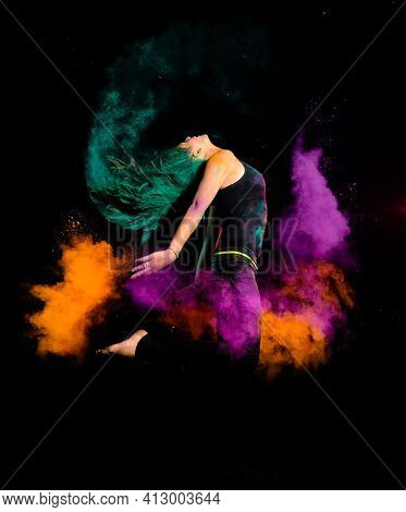 A Young Woman Makes A High Jump With A Explosion Of Dry Colorful Holi Powder. Holi Festival India