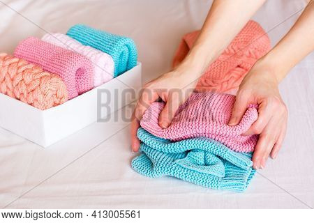 Organization And Order. Female Hands Fold Knitted Clothes Next To A Box With Neatly Folded Things