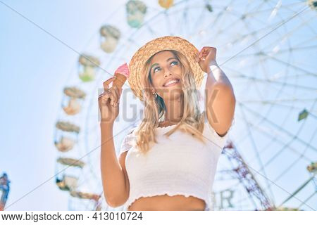 Young blonde tourist girl smiling happy eating ice cream at the fairground.