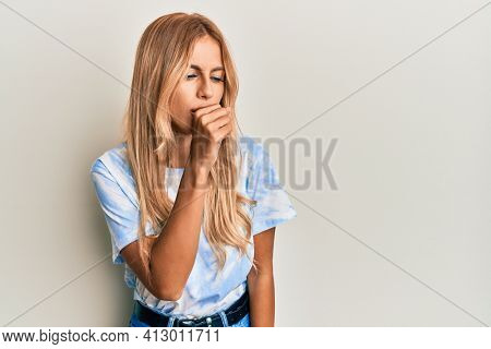 Beautiful blonde young woman wearing tye die tshirt feeling unwell and coughing as symptom for cold or bronchitis. health care concept.