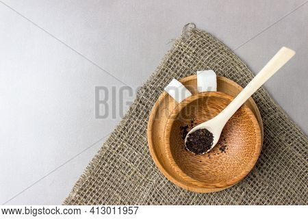 Two Sugar Cubes In A Wooden Plate And Spoon With Tea Leaves On Sackcloth On The Kitchen Table. Makin