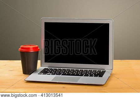Mocap Laptop With Blank Screen For Product Display And Coffee On A Wooden Table.