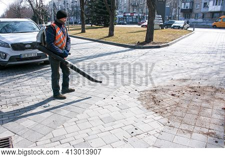 Dnepropetrovsk, Ukraine - 03.16.2021: A Worker On The Street In Early Spring Removes Leaves And Dust
