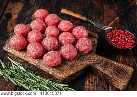 Uncooked Raw Meatballs From Ground Beef And Pork Meat With Rosemary. Dark Wooden Background. Top Vie