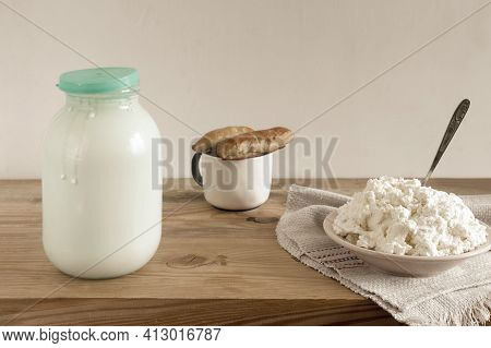 On The Wooden Table Is A Glass Jar Of Milk, A Plate Of Homemade Cottage Cheese And Pies. Front View,
