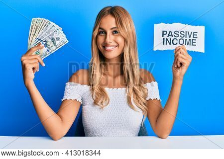 Beautiful blonde young woman holding dollars and passive income text smiling with a happy and cool smile on face. showing teeth.