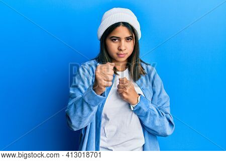 Young latin woman wearing cute wool cap ready to fight with fist defense gesture, angry and upset face, afraid of problem