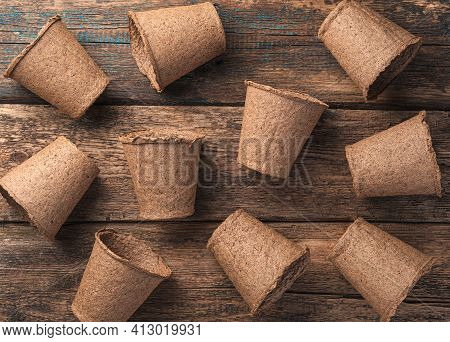Background With Randomly Arranged Peat Pots On A Wooden Table. Top View. The Concept Of Cultivation.