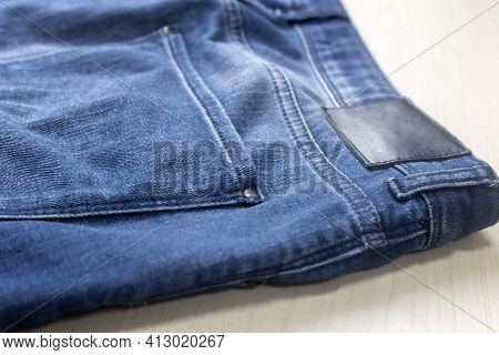 Fragment Of Blue Denim Trousers With A Back Pocket On A Light Background.