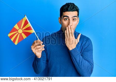 Handsome hispanic man holding macedonian flag covering mouth with hand, shocked and afraid for mistake. surprised expression