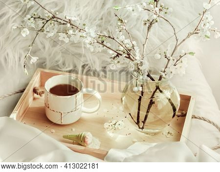 The Atmosphere Of A Romantic Morning, Coffee In Bed. Flowering Branches In A Vase And A Cup Of Coffe