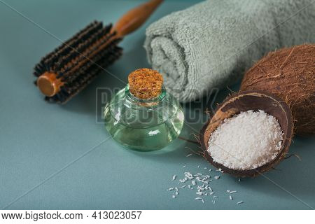 Coconut Oil In A Bottle With Coconuts, Towel And Hairbrush On Light Blue Background. Natural Beauty
