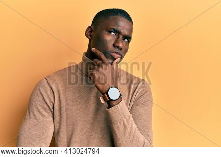 Young african american man wearing casual winter sweater thinking concentrated about doubt with finger on chin and looking up wondering