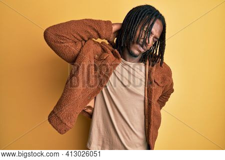 African american man with braids wearing brown retro jacket suffering of neck ache injury, touching neck with hand, muscular pain