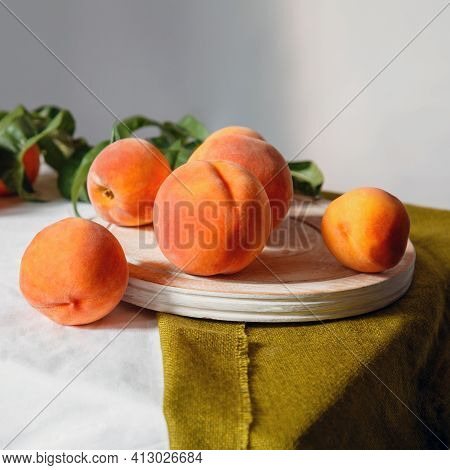 Peaches Fruit Still Life In Minimalistic Rustic Style. Peaches With Leaves On Table Board With White