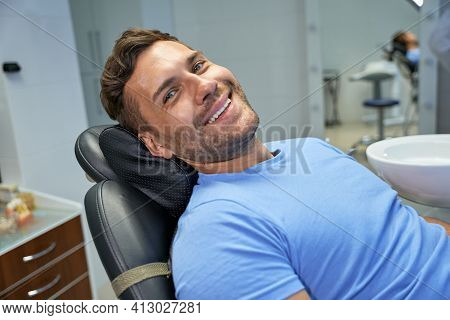 Joyous Patient Of Dental Clinic Resting In Dental Chair