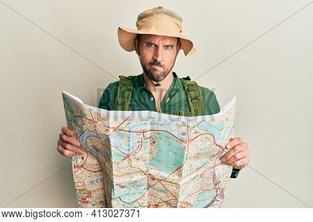 Handsome man with beard wearing explorer hat holding map skeptic and nervous, frowning upset because of problem. negative person.