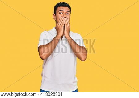 Young arab man wearing casual clothes laughing and embarrassed giggle covering mouth with hands, gossip and scandal concept