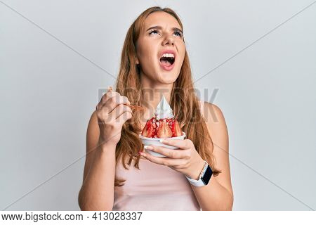 Young blonde woman eating strawberry ice cream angry and mad screaming frustrated and furious, shouting with anger looking up.