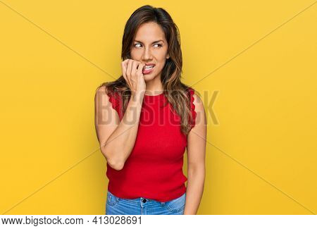 Young hispanic woman wearing casual clothes looking stressed and nervous with hands on mouth biting nails. anxiety problem.