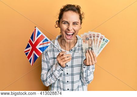 Young brunette woman holding uk flag and pounds banknotes smiling and laughing hard out loud because funny crazy joke.
