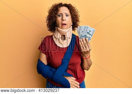 Beautiful middle age mature woman wearing cervical collar and sling holding insurance dollars in shock face, looking skeptical and sarcastic, surprised with open mouth