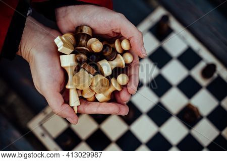 Close Up Of Chess Pieces In Hands Of Unrecognizable Woman. Unknown Female Holds Figures Of Chess In