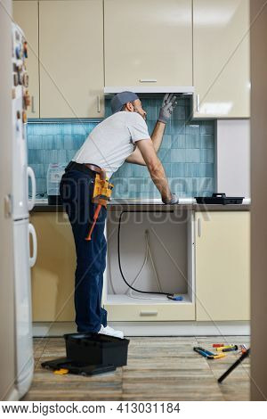 Fix Anything. Full Length Shot Of Young Handyman Examining A Kitchen Extractor Before Fixing It, Sta