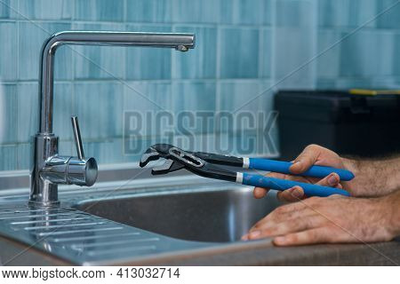 Close Up Shot Of Hand Of Professional Repairman Holding A Pipe Wrench While Fixing Faucet In The Kit