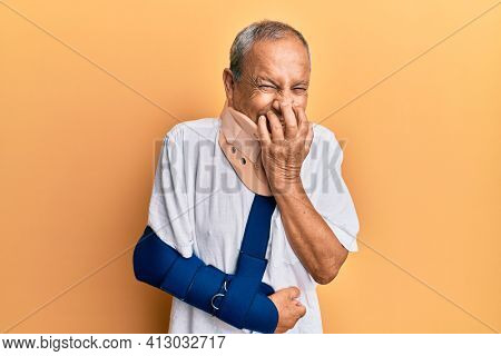 Handsome mature senior man wearing cervical collar and arm on sling laughing and embarrassed giggle covering mouth with hands, gossip and scandal concept