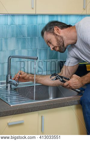 Fixing Leaky Faucet. Professional Plumber Looking Concentrated, Using Pipe Wrench While Examining An
