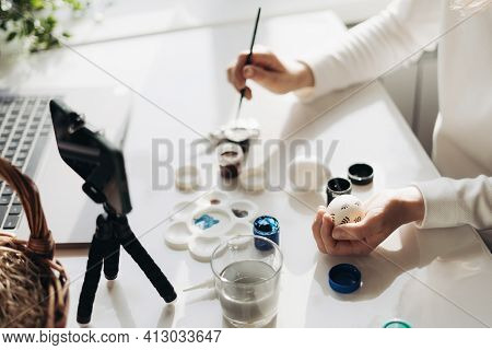 Hands Of Young Woman Blogger Live Streaming. Showing How To Decorate Easter Eggs. Tripod With Smartp