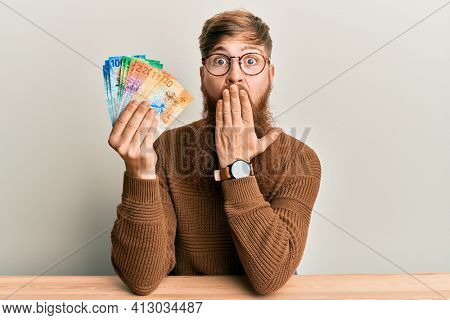 Young irish redhead man holding swiss franc banknotes sitting on the table covering mouth with hand, shocked and afraid for mistake. surprised expression