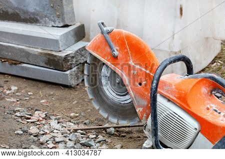 A Worn, Bright Orange Gasoline Cutter With A Diamond Cut-off Wheel Set Against A Background Of Concr