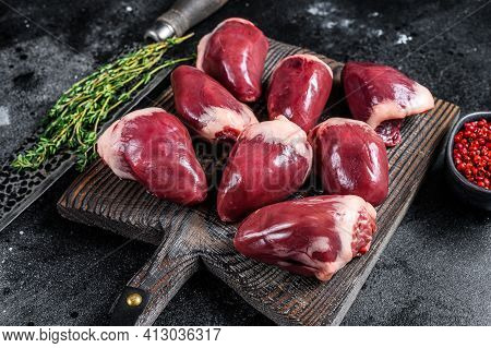 Raw Turkey Hearts Offal With Herbs And . Black Background. Top View
