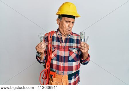 Senior hispanic man wearing handyman uniform holding led lightbulb and incandescent bulb in shock face, looking skeptical and sarcastic, surprised with open mouth